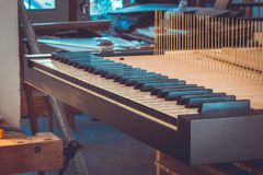 Construction of a piano, piano flaps in wood worksho, Grand Piano Construction. The sensitive inner mechanism of the piano translates all the nuances of your Stock Photo