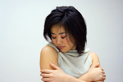 Sensitive Oriental woman. Sensitive beautiful Oriental woman in a white collared shirt Stock Photos