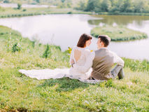 Sensitive outdoor back view of the hugging newlyweds sitting on the meadow and looking at each other. Stock Photography