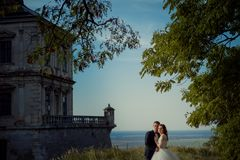 Sensitive outdoor portrait of the beautiful young newlywed couple tenderly hugging at he background of the old castle. And landscape Royalty Free Stock Photos