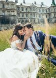 Sensitive outdoor portrait. The charming beautiful bride is troking the face of the handsome groom while sitting on the. Grass at the background of the old Stock Photo