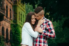 Sensitive outdoor portrait of the loving couple tenderly hugging. The young man is stroking the hand of his lover. royalty free stock photo