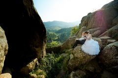 Sensitive outdoor wedding portrait. The bride is hugging the groom back while sitting on the rock at the background of. The beautiful sunny landscape Royalty Free Stock Image
