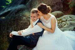 Sensitive portrait of the beautiful cheerful newlywed couple softly hugging on the rock. stock photography