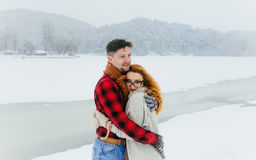 Sensitive portrait of the handsome man hugging his red head lover in the meadow covered with snow during the snowfall Stock Photos