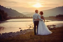 Sensitive wedding back shot. Peaceful beautiful newlyweds are hugging and looki at each other on the river bank during. The sunset stock photography