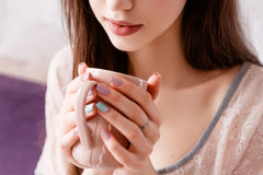 Sensitive young woman delights her morning coffee Royalty Free Stock Photography