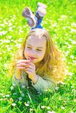 Sensitivity concept. Child enjoy spring sunny weather while lying at meadow with daisy flowers. Girl on smiling face royalty free stock photos