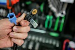Sensor del ABS en las manos de un mecánico de automóviles imagen de archivo