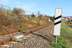 Sensor signaling the passage of the train on the railway track to activate the alarm at a road crossing. Mound of coarse gravel. With rails and sleepers for stock image