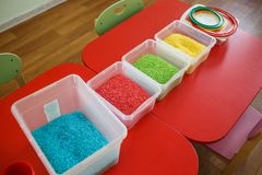 Sensory bin for toddlers with colourful rice on red table. Sensory box for toddlers with colourful rice on red table. Universal educational game in kindergarten Royalty Free Stock Photos