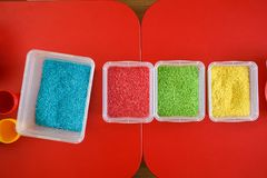 Sensory bin for toddlers with colourful rice on red table. Universal educational game. Sensory box for toddlers with colourful rice on red table. Top view Stock Images