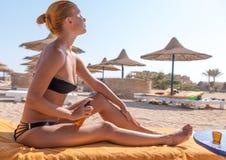 Sensous slim woman applying suntan oil. Sensous slim woman applying suntan lotion oil to her body at the beach Stock Photo