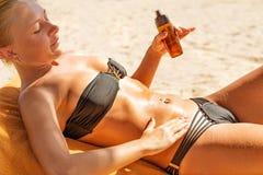 Sensous slim woman applying suntan oil. Sensous slim woman applying suntan lotion oil to her body at the beach Royalty Free Stock Images