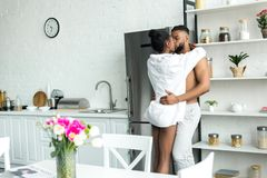 Sensual african american couple standing and kissing. At kitchen royalty free stock photos