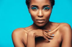 Sensual african woman wearing vivid makeup. Close up of sensual african woman wearing vivid makeup against blue background. Female model with beautiful skin Royalty Free Stock Images