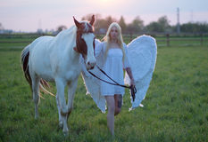 Sensual angel walking with the horse Royalty Free Stock Photo