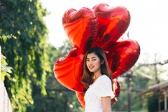 Sensual Asian female with balloons looking away royalty free stock images