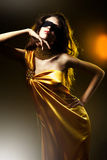 Sensual attractive woman in golden dress Stock Photography