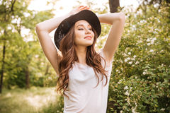 Sensual attractive young woman standing in park. Sensual attractive young woman in hat standing and posing in park Royalty Free Stock Photos