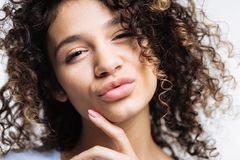 Close up of curly young woman pouting Royalty Free Stock Images