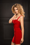 Sensual beautiful blonde woman posing in red dress. Girl with long curly hair Royalty Free Stock Image
