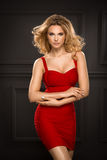 Sensual beautiful blonde woman. Posing in red dress. Girl with long curly hair Royalty Free Stock Images