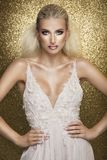 Sensual beautiful blonde woman posing in white dress over gold b. Ackground. Girl with long curly hair Stock Photos