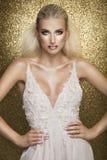 Sensual beautiful blonde woman posing in white dress over gold b Stock Photos