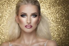 Sensual beautiful blonde woman posing in white dress over gold b Stock Images
