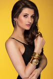 Sensual beautiful brunette woman posing in black dress and gold Stock Photo