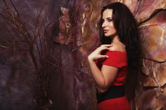 Sensual beautiful brunette woman posing in red dress. Art and fa. Young sensual beautiful blonde woman posing in red dress. Art and fashion concept Stock Photography