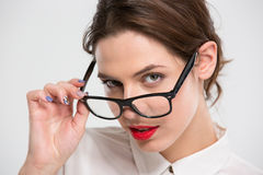 Sensual beautiful business woman with red lips looking over glasses Royalty Free Stock Image
