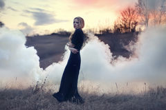 Sensual beautiful girl in smoke on nature royalty free stock photography