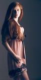 Sensual beautiful redheaded girl. Beautiful sensual redheaded girl in a pink dress and long hair Royalty Free Stock Image