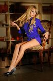 Gorgeous and sexy blonde woman on an elegant chair. Sensual and beauty girl naked on an elegant chair wearing a violet shirt