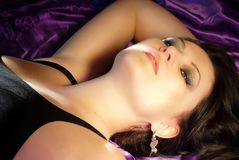 Sensual beauty woman portrait on purple silk bed royalty free stock photography