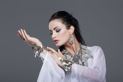 Sensual belly dancer performance portrait. On grey background stock photography