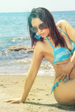 Sensual bikini woman on the sea beach with sunglasses. A woman in a swimsuit and sunglasses sitting on the beach at sea. Behind her, a blue sea and some rocks Royalty Free Stock Photos
