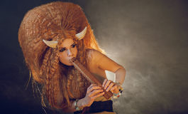 Sensual black eyed demon playing flute Royalty Free Stock Images