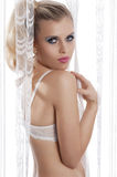 Sensual blond behind curtain with white bra Royalty Free Stock Photo