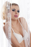 Sensual blond behind curtain with white bra with Royalty Free Stock Photo