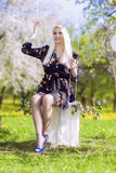Sensual Blond Female Relaxing In Spring Forest on Swing. Royalty Free Stock Image