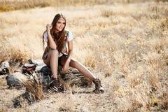 Sensual blond girl in field. Beautiful romantic girl outdoors. Beautiful teenage girl sitting on a tree stump in the field in sun light Royalty Free Stock Photo
