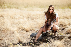 Sensual blond girl in field. Beauty Romantic Girl Outdoors. Beautiful teenage girl sitting on a tree stump in the field in sun light. Autumn Royalty Free Stock Photography