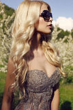 Sensual blond girl  in luxurious sequin dress with sunglasses Royalty Free Stock Images