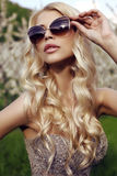 Sensual blond girl  in luxurious sequin dress with sunglasses Royalty Free Stock Photography