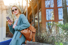Sensual blond girl relaxing on street with smartphone royalty free stock image