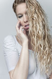 Sensual blond girl in wet shirt. Long hair Stock Images