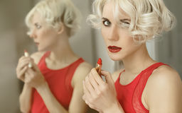 Sensual blond lady with red lipstick. Reflection in the mirror Royalty Free Stock Image